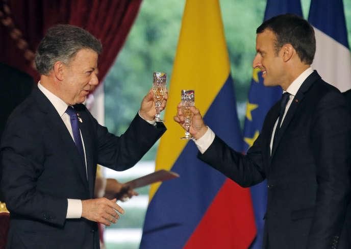 Le président colombien Juan Manuel Santos trinque avec le président français Emmanuel Macron lors d'un dîner officiel à l'Elysée à Paris, le 21 juin.