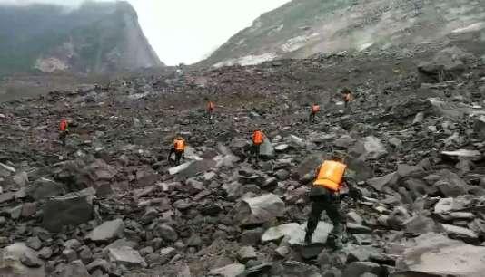Des secouristes parcourent le terrain à la recherche des disparus, le 24 juin.