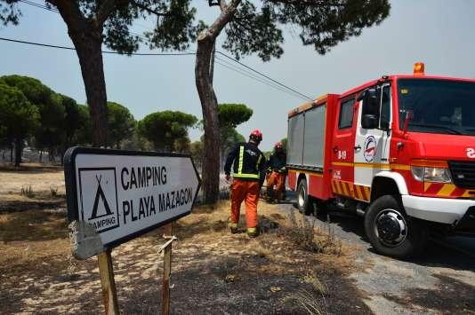 Les pompiers préparent leurs matériels avant de partir combattre les flammes, près du camping « Palya Mazagon », dans le sud de l'Espagne, évacué le 25 juin 2017. (AFP / CRISTINA QUICLER)