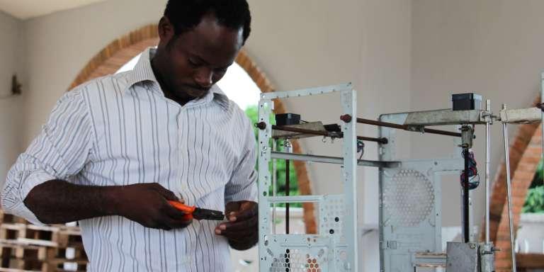 Un membre de la start-up Woebots en pleine construction d'une imprimante 3D, à Lomé, au Togo.