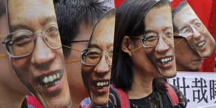 Des manifestants portent des masques de l'intellectuel dissident Liu Xiaobo, devant leChinese Liaison Office à Hongkong, le 27 juin 2017.