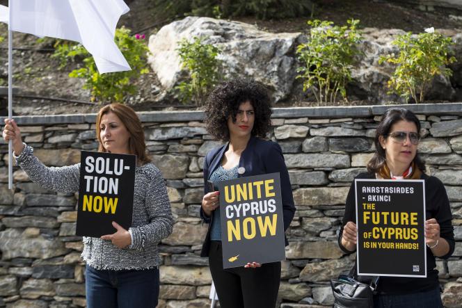 Des partisanes du processus de paix chypriote arborent des affiches réclamant une solution au conflit qui pollue l'île méditerranéenne depuis plus de quarante ans, à l'aube d'une nouvelle série de pourparlers, à Crans-Montana (Suisse), le 28juin.