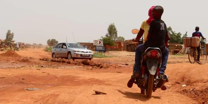 A Tampouy, dans le nord-ouest de Ouagadougou, motards et automobilistes attendent le goudronnage de la route principale, difficilement praticable.