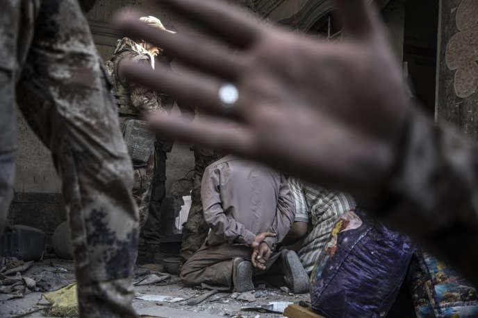 Les forces spéciales irakiennes arrêtent trois hommes soupçonnés d'être membres de l'organisation Etat islamique, à Mossoul (Irak), le 29 juin.