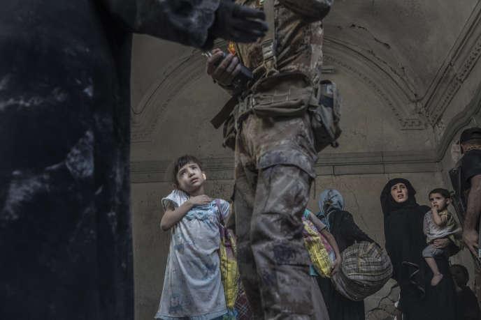 L'armée, la police fédérale et les forces spéciales des services du contre-terrorisme irakien découvrent une famille en se frayant un chemin à la masse dans les décombres de la ville de Mossoul, le 30 juin.