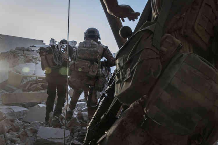 Un par un, les soldats s'élancent sur des monticules de débris, exposés au feu des snipers de l'EI.