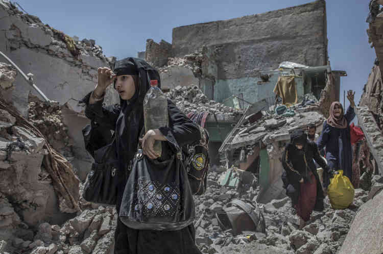 Des civils sortent de leur maison, dans les décombres des bâtiments détruits par les bombardements.