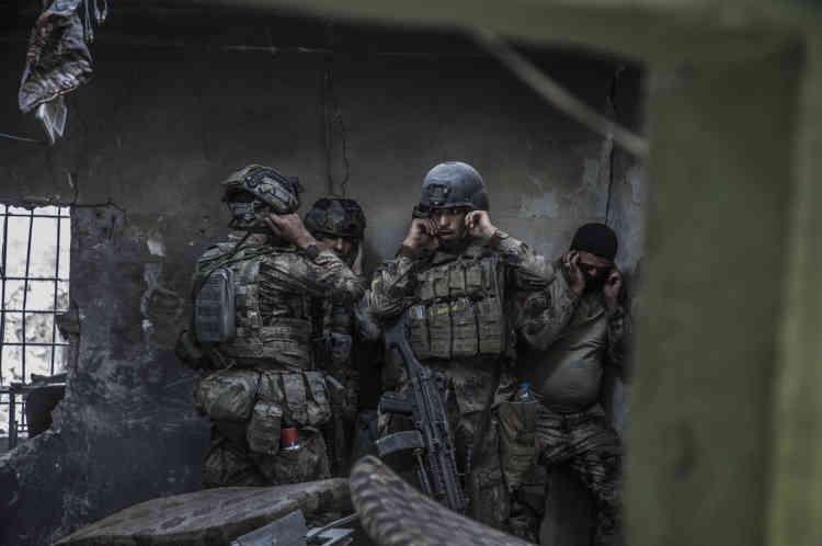 Des soldats attendent l'explosion pour pouvoir pénétrer dans la maison attenante.