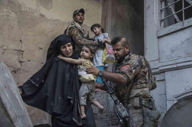 Deux femmes et leurs enfants sont évacués par des soldats.