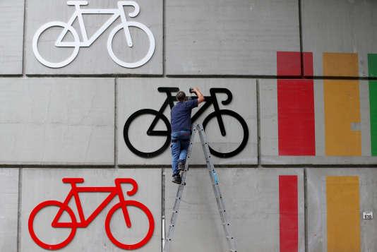 En préparation du départ du Tour de France, un ouvrier décore un pont sur le parcours de la première étape, le 29 juin.