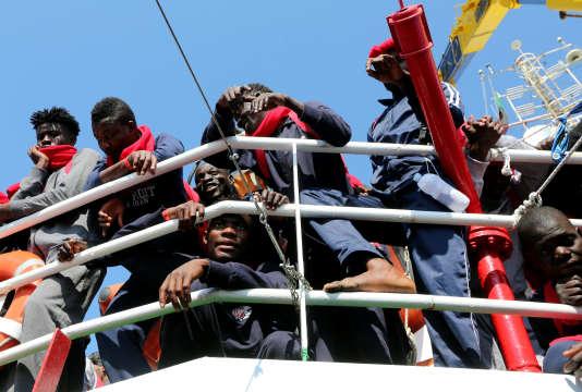 Des migrants attendent de débarquer dans le port de Crotone, en Italie, après avoir été sauvés par l'équipe «Save the Children» en Méditerranée au large de la côte de Libye, le 21 juin 2017.