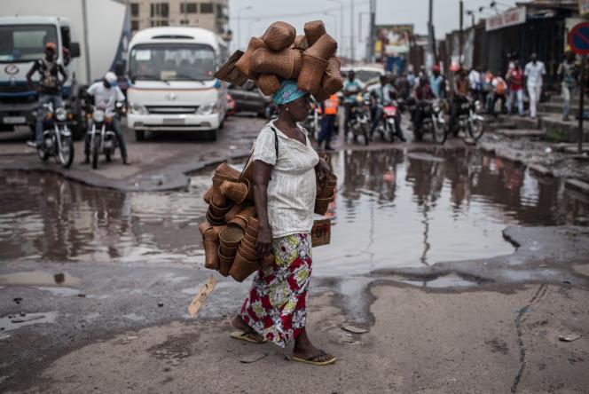 Une femme portant des paniers traverse une rue dans le quartier de Matonge, à Kinshasa, en 2015.