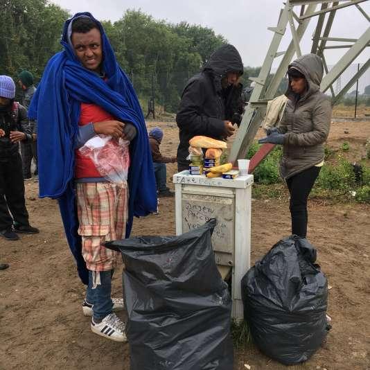 Ce jeune érythréen de 16 ans demande à pouvoir prendre une douche, le 28 juin 2016, dans la zone industrielle des Dunes, à Calais, lors d'une distribution de nourriture par une association.