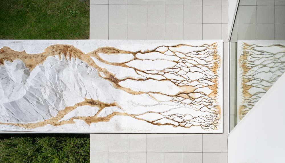 «Œuvre conçue pour le jardin de la Fondation par Sylvie de Meurville (1956), le Mont d'ici est un hommage à la montagne du Hartmannswillerkopf, au pied de laquelle est niché le village de Wattwiller. Tel un corps de femme couché, l'installation se déploie dans le prolongement du bâtiment du Centre d'Art : un véritable dialogue entre l'intérieur et l'extérieur. »