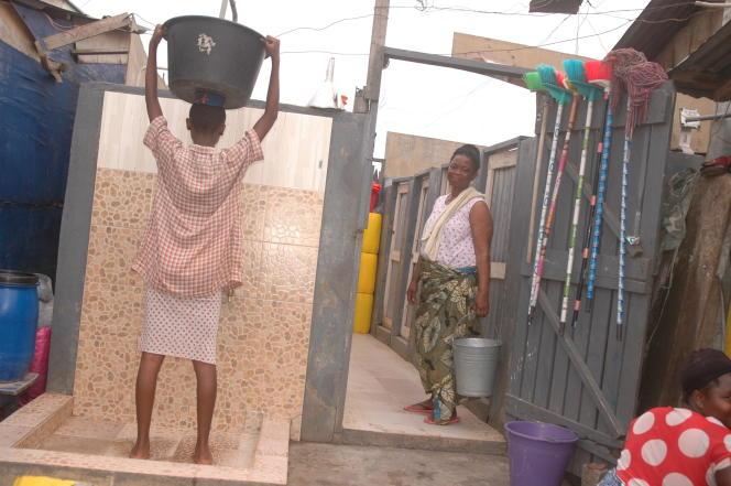 Janet Adu aux douches publiques, à Ashaiman, un bidonville proche d'Accra, en juin 2017.
