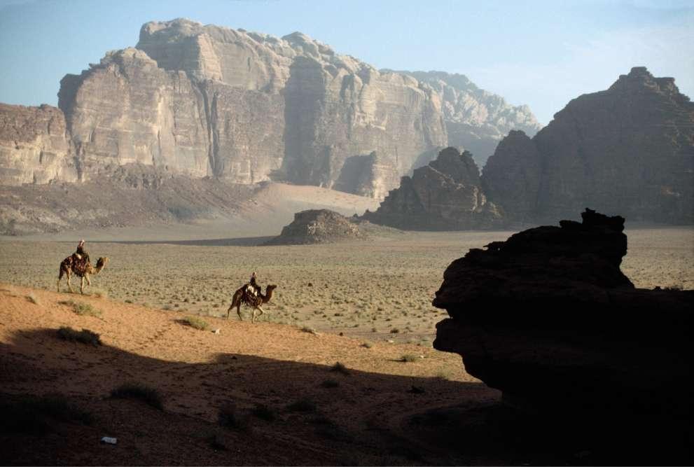 Sur ce cliché de 1995, des soldats de l'armée jordanienne traversent le désert de Wadi Rum à dos de chameau. Cette photo est issue de la série « Sur les traces de Lawrence d'Arabie», de Harry Gruyaert, qui a refait le parcours de la révolte arabe contre l'Empire ottoman, entre1916 et1918, muni de ses objectifs. Le 6juillet, il y a tout juste centans, les forces arabes menées par Fayçal ben Hussein etThomas Edward Lawrence, et soutenues par la marine britannique, remportaient une victoire stratégique en s'emparant du port d'Aqaba, dans l'actuelle Jordanie. Ce conflit s'inscrit en marge de la première guerre mondiale, les Britanniques souhaitant affaiblir les Ottomans, alliés de l'Allemagne. Il est aussi l'une des premières grandes manifestations du nationalisme arabe.