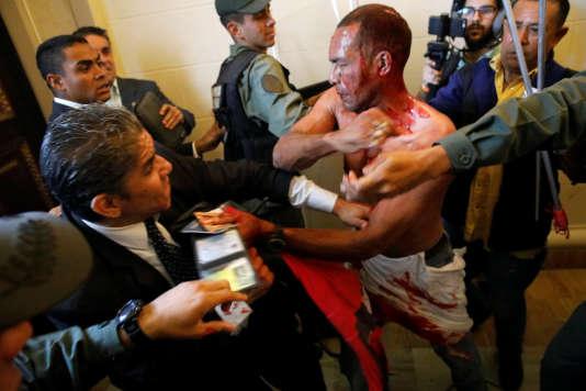 Un partisan du président Maduro en sang tente de quitter le Parlement après s'y être introduit de force et avoir agressé des députés, mercredi 5 juillet à Caracas.