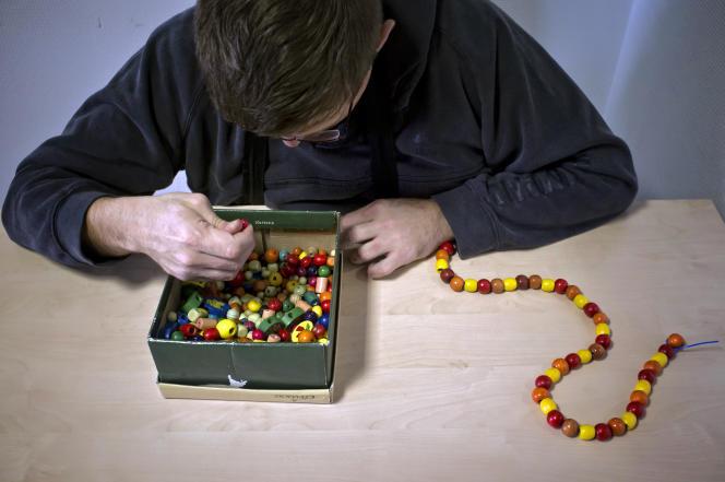 Une personnes autiste réalise un collier de perles avec l'aide du personnel du centre médical L'Envolée, à L'Isle-d'Abeau (Isère), en 2012.