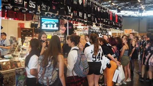 Les écrans diffusant de la K-pop attirent des grappes de fans.