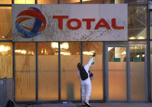 Un militant de Greenpeace dégrade l'enseigne du groupe Total au siège de La Défense (Hauts-de-Seine), le 27 mars.