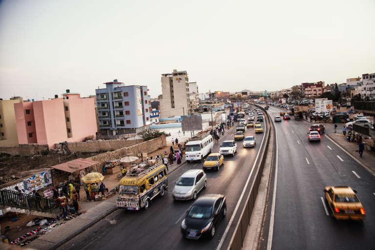 Dakar, en mai 2017. A gauche, un«brésilien» (minibus jaune et bleu) précède un«ndiaga ndiaye» (blanc).