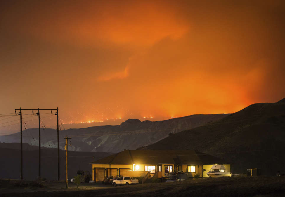 De gigantesques incendies ont entraîné l'évacuation de quelque 10 000 personnes dans l'ouest du Canada et de 8 000 personnes en Californie. (Darryl Dyck/The Canadian Press via AP)