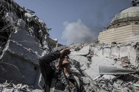 Un membre des forces spéciales irakiennes surveille le ciel après une frappe de la coalition anti-EI, à Mossoul, le 10 juillet.