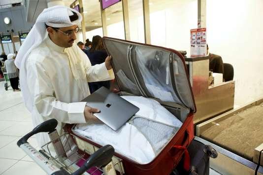 Un Koweïti met son ordinateur portable en soute pour son vol vers les Etats-Unis, le 23 mars.