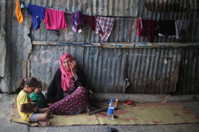Une femme palestinienne et ses petits-enfants dans leur maison du camp de réfugués de Khan Younès, dans le sud de la bande de Gaza, le 11 juillet.