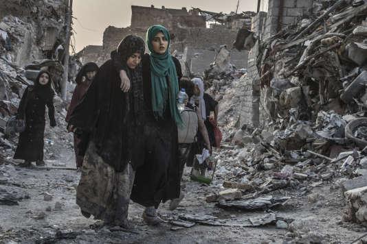Des familles traversent la ligne de front au lever du jour, alors que les forces spéciales irakiennes combattent encore, le 10 juillet.