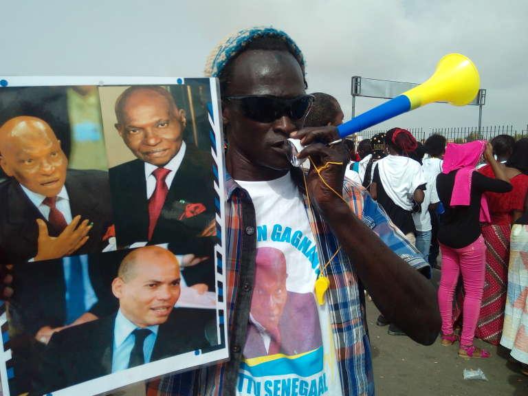 Un partisan de l'ex-président Abdoulaye Wade et de son fils Karim venu l'accueillir à son arrivée à Dakar le 10 juillet 2017.