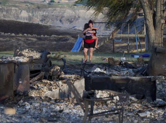 Une femme porte sa fille au milieu des décombres de leur maison, près d'Ashcroft, en Colombie-Britannique, le 9 juillet.
