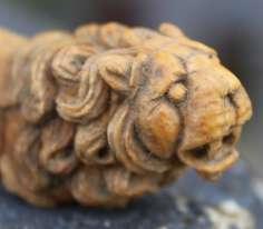 Détail de la tête où l'on peut apprécier le talent du sculpteur dans la crinière ou les crocs. Au total le lion mesure à peine plus de 5 centimètres.