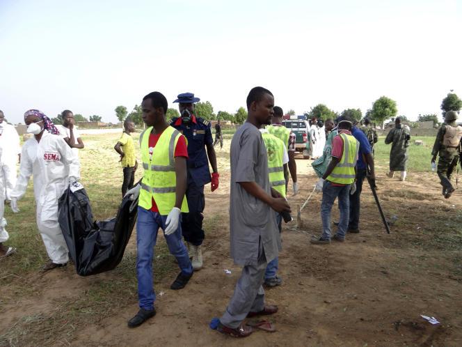 Des secouristes portent le corps d'une victimede Boko Haram, le 12 juillet près d'un village deMaiduguri, au Nigeria. Mardi, l'attaque d'une équipe pétrolière faisait 50 morts dans la région.