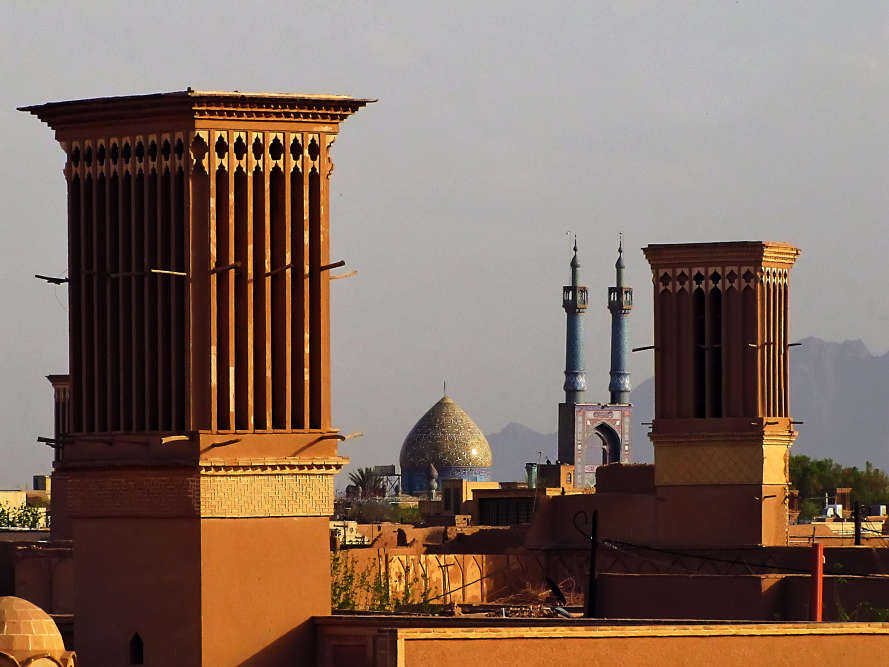 Vue d'ensemble de la ville historique de Yazd en République islamique d'Iran. C'est un témoignage vivant de l'utilisation des ressources limitées pour assurer la survie dans le désert. L'eau est amenée en ville par un système de qanats – ouvrage destiné à la captation d'une nappe d'eau souterraine. Les édifices sont construits en terre. La ville a échappé aux tendances à la modernisation qui ont détruit de nombreuses villes traditionnelles en terre.