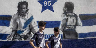 Tomás Trúcolo (13 ans) and Agustín Madrussan (14 ans), deux enfants du club de Lamadrid, posent devant une fresque en l'honneur des joueurs qui ont marqué le club.