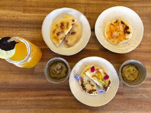 Galettes de maïs, aji de mani (sauce aux cacahuètes), caviar d'aubergines et «michelada», boisson à base de bière et de citron.