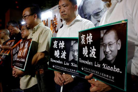 Des militants pour la démocratie pleurent la mort de l'opposant Liu Xiaobo, devant le bureau de liaisondugouvernement central chinois à Hongkong, le 13 juillet.
