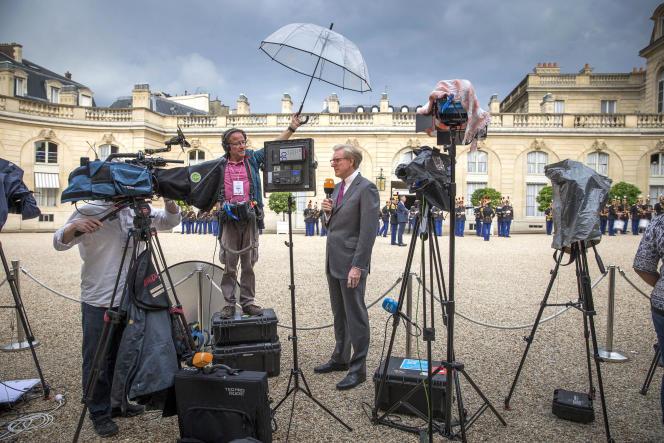 Dans la cour de l'Elysée, les journalistes de télévison au travail, le 13 juillet.