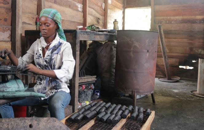 Simone Mboule, stagiaire chez Kemit Ecology, moule le charbon écologique pour en faire des briquettes.