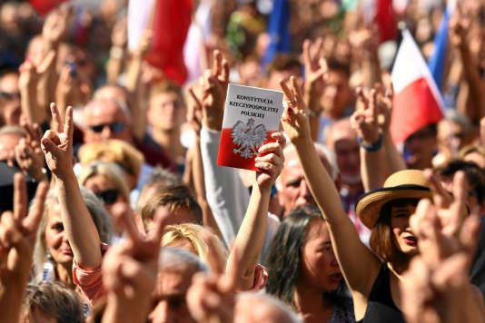 Des manifestants brandissant la Constitution polonaise lors d'un rassemblement àCracovie, dimanche 16 juillet.