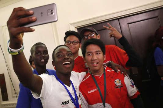 Mawuena Yves Date, du Togo, prend un selfie avec des lycéens de l'équipe sud-soudanaise et de l'équipe indonésienne.