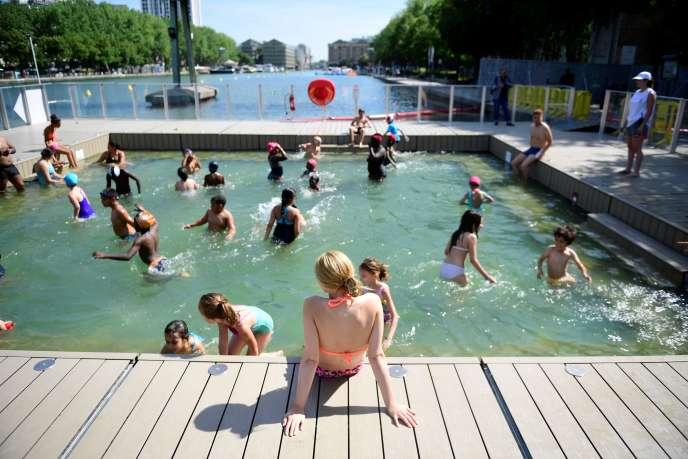 Des enfants se baignent dans le petit bassin de 40 centimètres d'eau inauguré mardi 18juillet, dans le bassin de La Villette, à Paris.