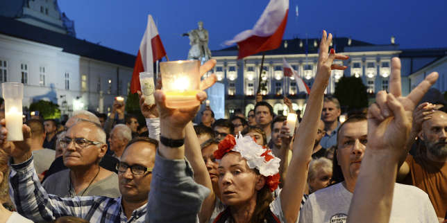Protesters raise candles during a protest in front of the presidential palace, as they urge Polish President Andrzej Duda to reject a bill changing the judiciary system, in Warsaw, Poland, Tuesday, July 18, 2017. Poland's lawmakers continue a heated debate about the controversial draft law by the ruling populist party that will reorganize the work of the Supreme Court, which, the opposition says, will subordinate the court to the justice minister. (AP Photo/Alik Keplicz)
