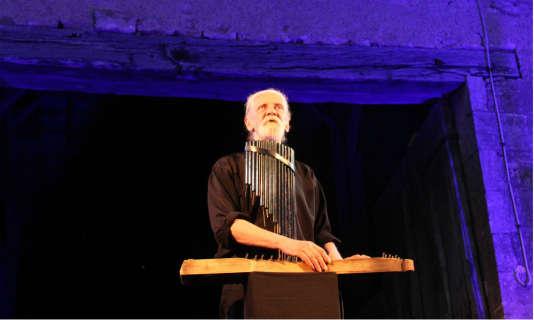 Michel Hindenoch joue de la flûte de paon et de la cithare hongroise en même temps qu'il conte