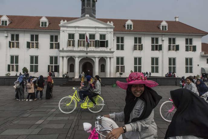 Adolescentes à vélo devant l'ancienne mairie de Batavia (le nom de Djakarta à l'époque coloniale hollandaise), aujourd'hui un musée, le 24 mai.