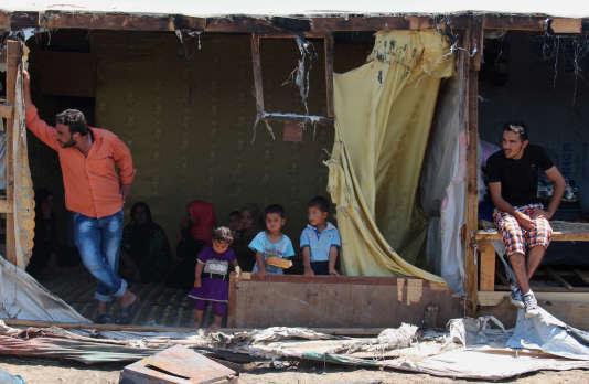 Des réfugiés syriens dans leur camp gravement endommagé par un incendie, à Bar Elias, dans la vallée de la Bekaa, le 4 juillet.
