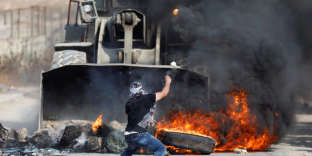 A Palestinian man hurls stones at an Israeli military machinery during clashes with Israeli troops in the West Bank village of Khobar near Ramallah July 22, 2017. REUTERS/Mohamad Torokman