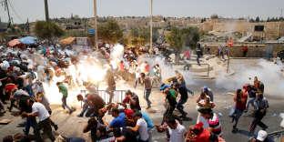 Des fidèles musulmans fuient les gaz lacrimogènes utilisés par les forces israéliennes, à l'extérieur de la vieille ville de Jérusalem, le 21 juillet.