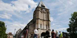 (FILES) This file photo taken on July 28, 2016 shows people gathering near floral in front of the church of Saint-Etienne-du-Rouvray, northern France, where French priest Jacques Hamel was killed on July 26 in the church during a hostage-taking claimed by Islamic State group. The 84-year-old Jacques Hamel died on July 26, 2016 after his throat was slit after two attackers stormed the church during a morning mass, taking the five people inside hostage, including the priest, interior ministry spokesman said. / AFP / CHARLY TRIBALLEAU